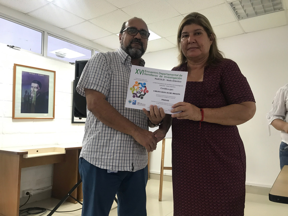 Carlota Olivia Sucre Holguín (Semillero REMEFES, Teología) recibiendo reconocimiento del Vicerrector Milcíades Púa.
